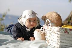 Das Baby liegt auf einer Decke am Strand stockfoto