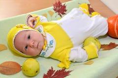 Das Baby liegt auf einer Tabelle unter Herbstlaub und Frucht Stockbilder