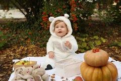 Das Baby, das mit Kürbis aufwerfen und die Spielwaren unter Bäumen im Herbst stellen gleich Stockfotos