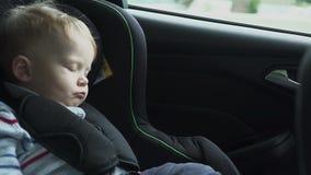 Das Baby schläft im Auto auf die Art Schlafendes Kind am hinteren Stuhl im Auto in der Zeitlupe HD stock footage