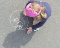 Das Baby zeichnet auf die Pflasterung am Kopf Stockfotografie