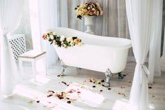 Das Badezimmer ist in einem hellen Raum, der mit Blumen und den Blumenbl?ttern von Rosen verziert wird stockfoto