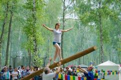 Das Balancieren des jungen Mädchens geht auf einen langen schwingklotz stockbild