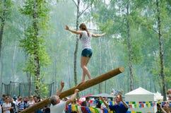 Das Balancieren des jungen Mädchens geht auf einen langen schwingklotz stockfotos