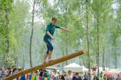 Das Balancieren des jungen Mannes geht auf einen langen schwingklotz stockfotografie