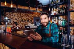 Das barista barma mit einer Tablette lächelt am Arbeitsplatz in der Stange Lizenzfreie Stockbilder