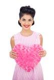 Das begeisterte Modell des schwarzen Haares, das ein rosa Herz hält, formte Kissen Lizenzfreies Stockbild