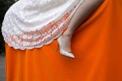 Das Bein der Frau im weißen Schuh des hohen Absatzes Stockfoto