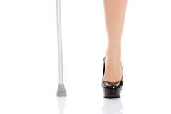 Das Bein und eine Krücke der Frau. Behindertes Konzept. lizenzfreie stockbilder