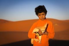 Das Berberkind, das einen Wüstenfuchs hält, wirft in den Erg Chebbi-Dünen in Marokko auf Stockfotografie