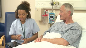 Das Bett Krankenschwester-Sitting By Male-Patienten unter Verwendung Digital-Tablets stock video
