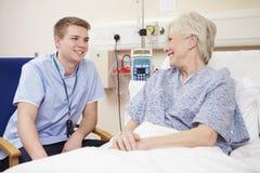 Das Bett männlichen Krankenschwester-Sitting By Female-Patienten im Krankenhaus stockbilder