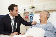 Das Bett Patienten Doktor-Sitting By Male im Krankenhaus stockbild