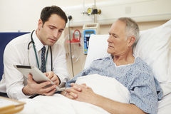 Das Bett Patienten Doktor-Sitting By Male unter Verwendung Digital-Tablets stockbild