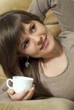 Das Bezaubern der recht schönen Frau hält ein Cup an stockfotografie