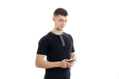 Das Bezaubern, lächelnder junger Kerl hält Handy lizenzfreie stockfotografie