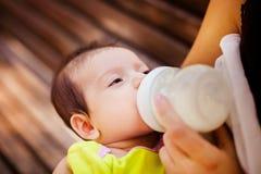 Das Bild der Frau, die ihr Baby von einer kleinen Flasche der Kinder einzieht Lizenzfreies Stockfoto