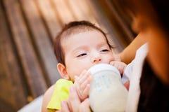 Das Bild der Frau, die ihr Baby von einer kleinen Flasche der Kinder einzieht Stockbild
