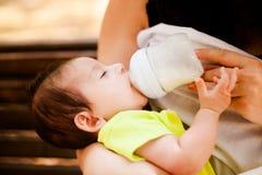 Das Bild der Frau, die ihr Baby von einer kleinen Flasche der Kinder einzieht Stockbilder