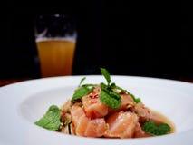 Das Bild des würzigen Lachssalats auf weißer Platte und einem Glas von stockfoto