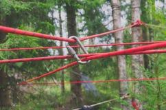 Das Bild ist ein carabiner Haken mit einem roten Seil für das Klettern und Sicherheit Stockfoto