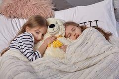 Das Bild von zwei kleinen Schwestern wacht morgens auf stockbild