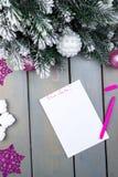 Das Blatt Papier, rosa Bleistifte und Weihnachtsdekorationen auf einem hölzernen Hintergrund Konzept des neuen Jahres und des Wei Stockfotos