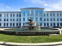 Das blaue schöne Gebäude der staatlichen Universität von Batumi und des Brunnens vor ihm Batumi, Georgia, am 17. April 2019 lizenzfreies stockbild
