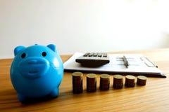 Das blaue Sparschwein mit Geschäft, sparen Geld Ei auf goldenem Hintergrund stockfoto