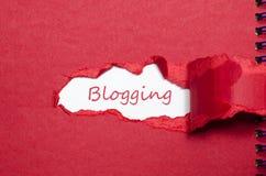 Das blogging Erscheinen des Wortes hinter heftigem Papier Lizenzfreies Stockfoto
