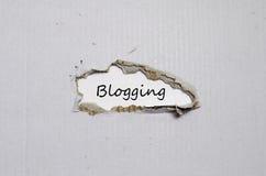 Das blogging Erscheinen des Wortes hinter heftigem Papier Stockfotos