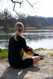 Das blonde Athletenmädchen, das auf dem Boden sitzt, um sich, nachdem sie mit Wasserflasche unter einem Baum auf einem Seeufer, z Stockfoto