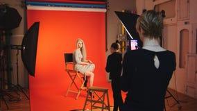 Das blonde attraktive Mädchen, das für Fotografen aufwirft, Maskenbildner machen ein Foto mit Smartphone, Modebühne hinter dem vo Lizenzfreies Stockfoto