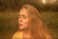 Das blonde behaarte Mädchen, das weg mit ihren Augen grimasing und geschaut worden sein würde, schloss Retro- Farbe Stockfotografie