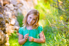 Das blonde Kindermädchen, das mit purpurroter Blume lächelt, entspannte sich im Freien Stockfoto