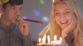 Das blonde lächelnde Mädchen und ein Mann in den Geburtstagshüten, die vor wenigem Kuchen mit Kerzen sitzen Die Frau hat Geburtst stock video footage