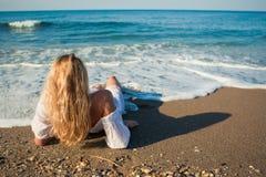 Das blonde Lügen auf dem Strand und sehen zum Ozean Lizenzfreie Stockfotografie