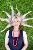 Das blonde Legen auf ein Gras mit dem zerstreuten Haar Lizenzfreies Stockbild