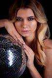 Das blonde Legen im Stil Abba hält einen Discoball Die Ära der Disco Nachtclub, tanzend Stockfotografie