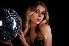 Das blonde Legen im Stil Abba hält einen Discoball Die Ära der Disco Nachtclub, tanzend Stockbilder
