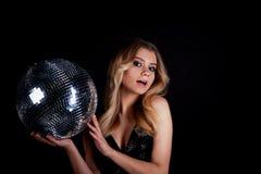 Das blonde Legen im Stil Abba hält einen Discoball Die Ära der Disco Nachtclub, tanzend Lizenzfreies Stockbild