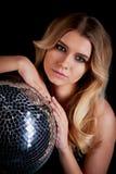 Das blonde Legen im Stil Abba hält einen Discoball Die Ära der Disco Nachtclub, tanzend Stockfoto