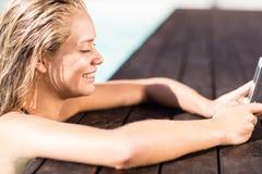 Das blonde Lehnen auf Pools umranden und die Anwendung von Smartphone Stockbild