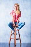 Das blonde Mädchen, das auf einem Stuhl mit den breiten Beinen aufwirft, öffnen sich Lizenzfreie Stockbilder