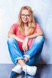 Das blonde Mädchen, das Gläser trägt, wirft beim Sitzen auf dem Boden auf Lizenzfreies Stockbild