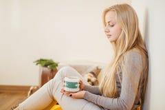 Das blonde Mädchen, das ihren Kaffee trinkt, essen Plätzchen und lasen ein Buch Lizenzfreie Stockbilder