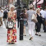 Das blonde Mädchen in den Gläsern und in langem Kleid, die nach Informationen über ihr Telefon zwischen einer Menge suchen Lizenzfreie Stockfotografie