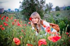 Das blonde Mädchen in den roten Mohnblumen Lizenzfreie Stockfotos