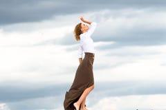 Das blonde Mädchen geht, den Wind zu treffen Lizenzfreie Stockfotos
