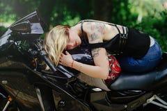 Das blonde Mädchen liegt auf einem Motorrad, lächelt Augen, sinnlich und nett, schließt Haar ihre Augen Lizenzfreies Stockbild